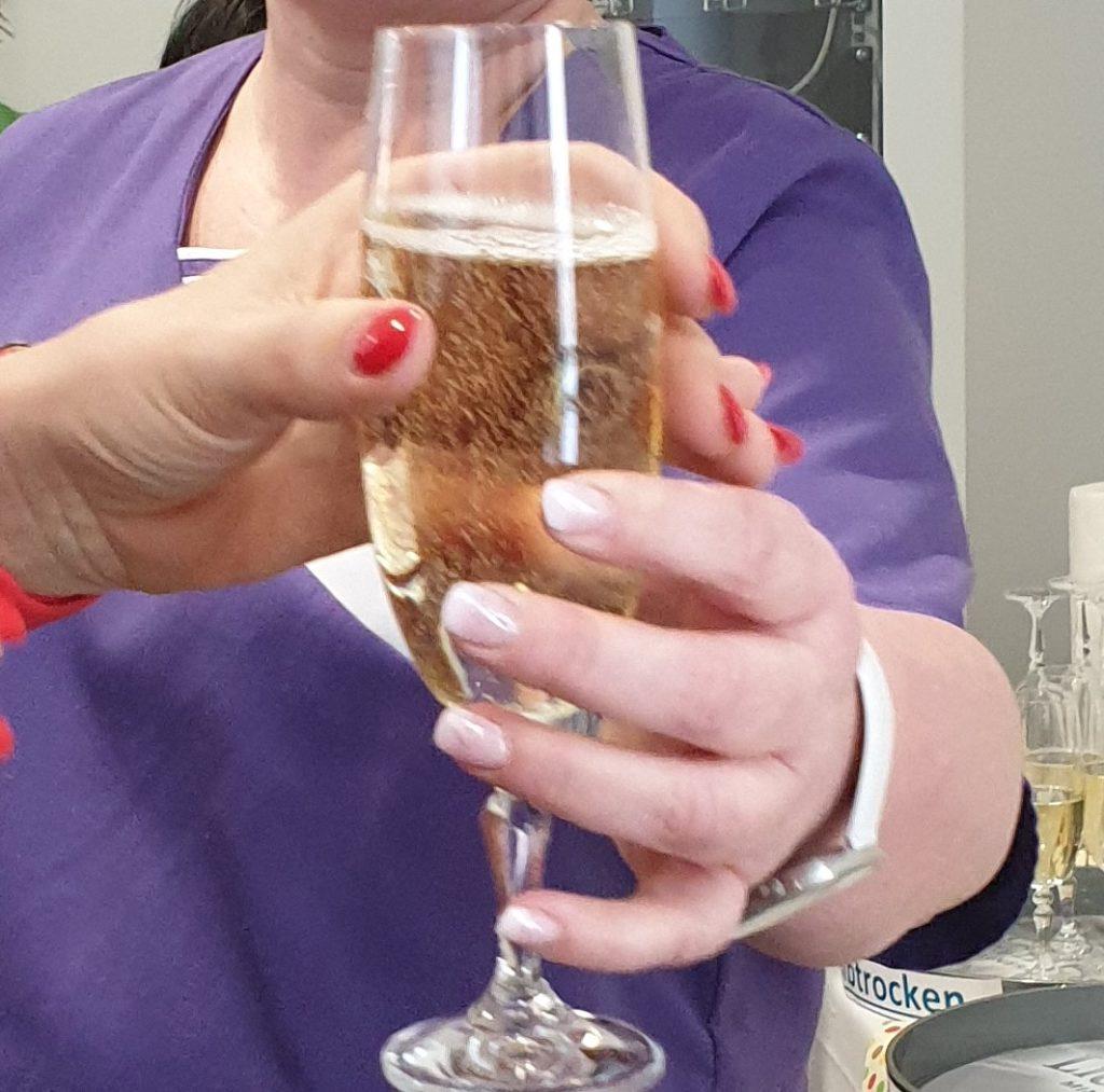 Zwei Frauenhände halten ein gefülltes Sektglas.