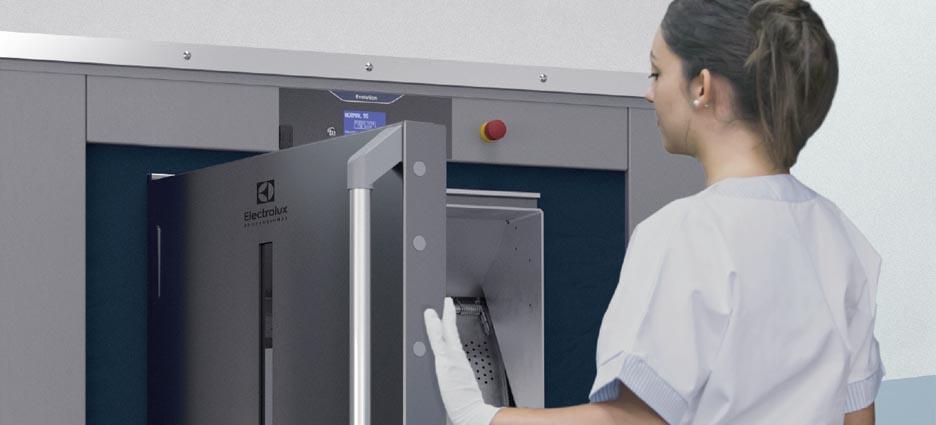 Eine junge Frau öffnet die Tür einer Hygienewaschmaschine